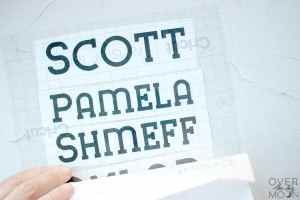 Vinyl cutouts of the names Scott, Pamela, Shmeff with transfer tape being applied.