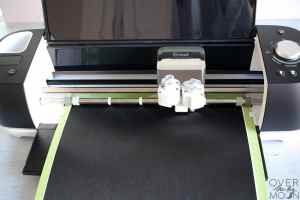 A black Cricut Explore Air 2, with a mat loaded with black vinyl into the machine.