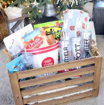 A wooden crate filled with personalized tumblers, popcorn buckets, snack tray, snacks and a blanket with milk and cookies on it.