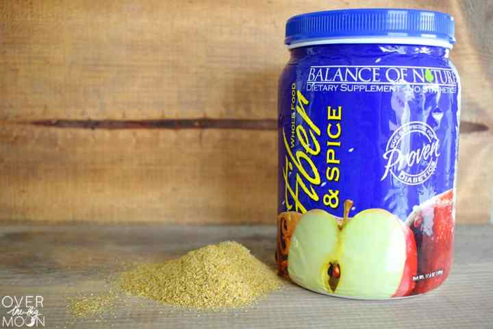 A big blue canisters of Balance of Nature Fiber and Spice with a pile of the product on the left.