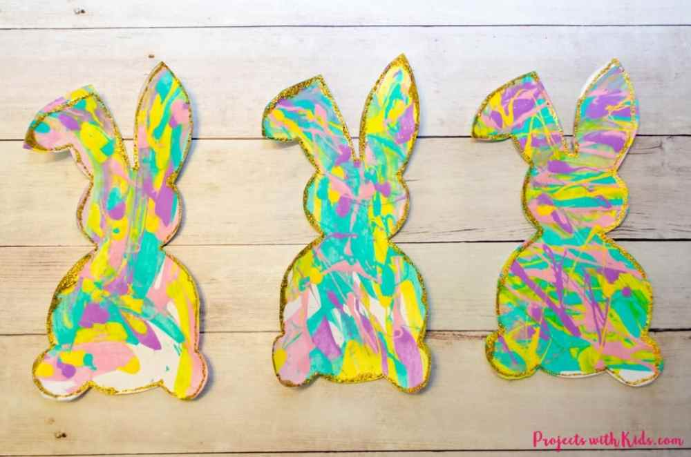 Bunny crafts made with paint and paper cutouts. Using an array of colors in a splattered pattern.