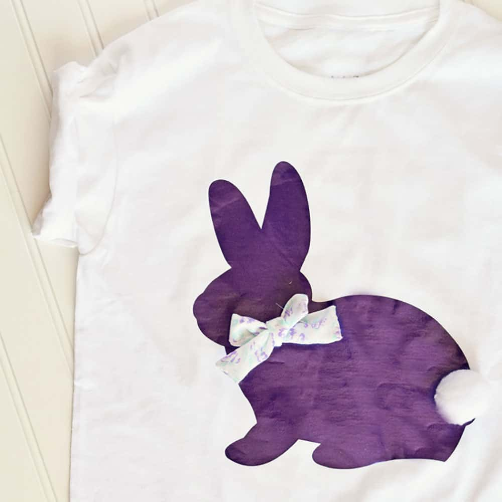 A white shirt with a purple bunny on it with a ribbon on the bunnies neck and a pom pom bunny tail.