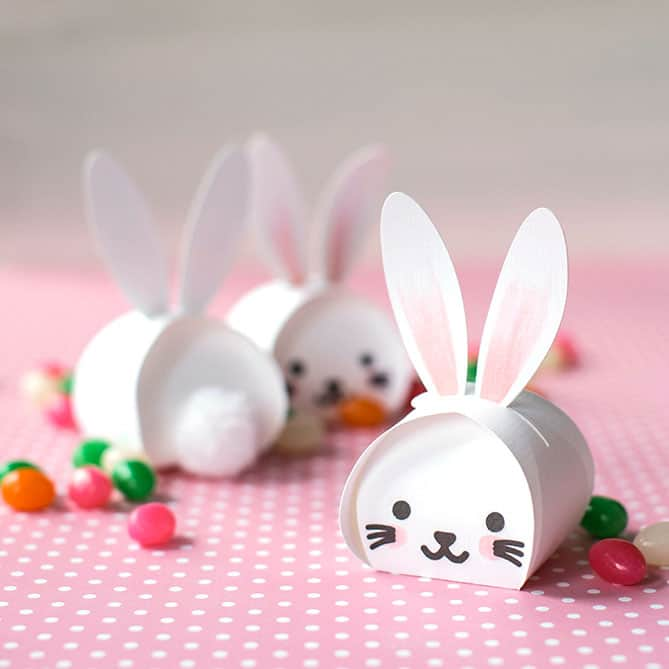 A bunny treat box that can be made using paper and some glue. Use a pom pom for a bunny tail. There are jelly beans around the treat boxes.