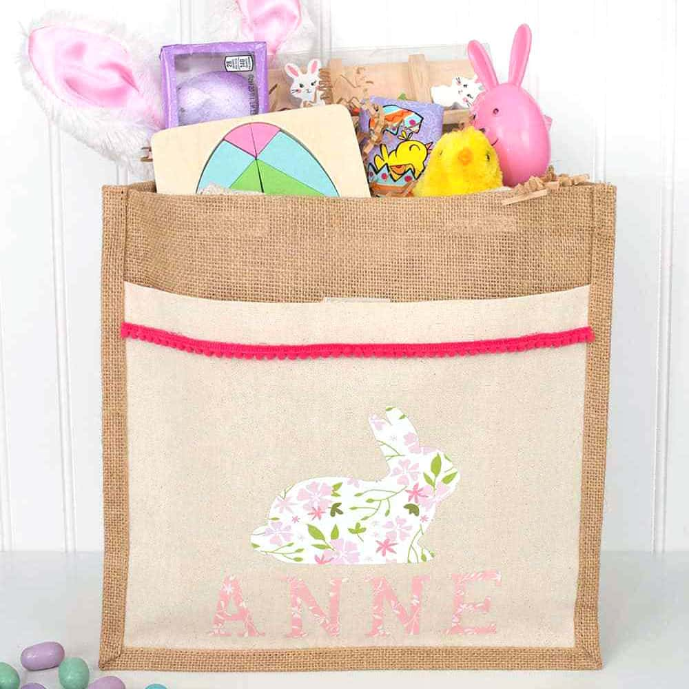 A canvas and burlap bag, personalized using Iron On Vinyl and trim. The Iron On is in the the shape of a bunny and the name Anne. Inside the bag are fun personalized Easter items such as candy and games.