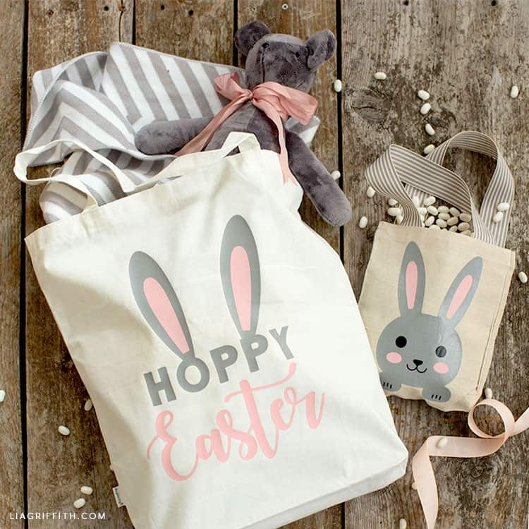 Two cute canvas bags customized for Easter. The one on the left says Hoppy Easter with two bunny ears coming out of the word Hoppy. The second smaller bag has a bunny on it. Both were personalized using Cricut Iron On.