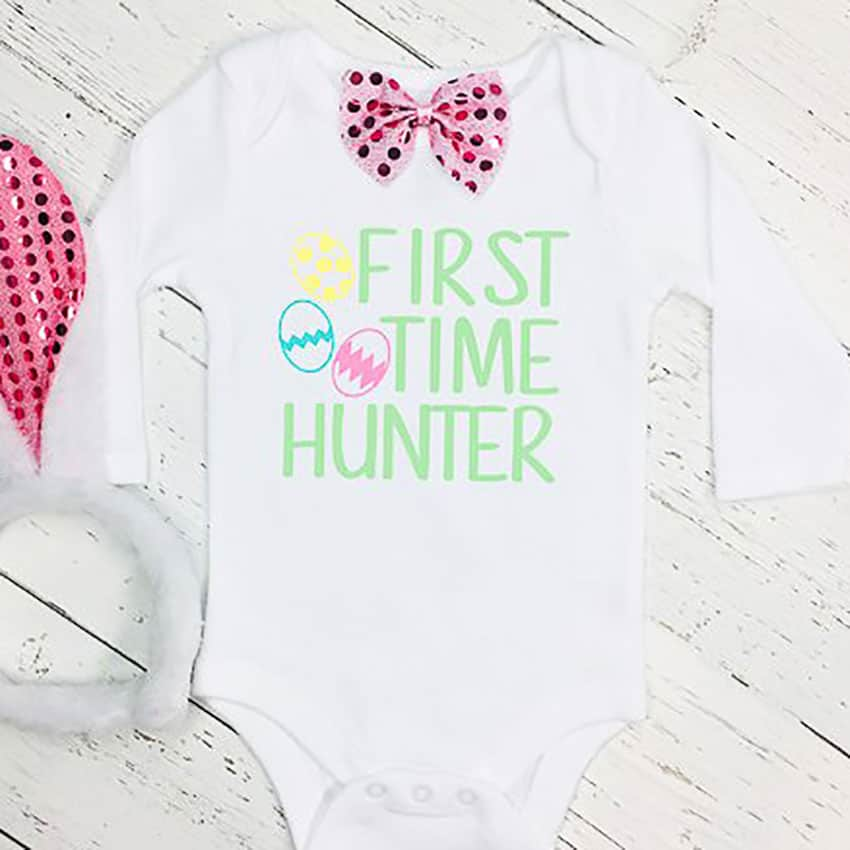 A white onesie that says First Time Hunger in Green with a yellow, blue and pink easter eggs next to it.