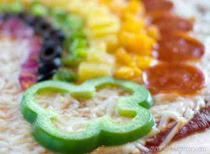 A close up picture of a green pepper cut to look like a clover at the edge of the a pizza with a rainbow made of toppings.