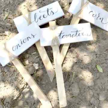 4 Garden Markers made from wood and twine that have the words beets, carrots, tomatoes and onions on them.