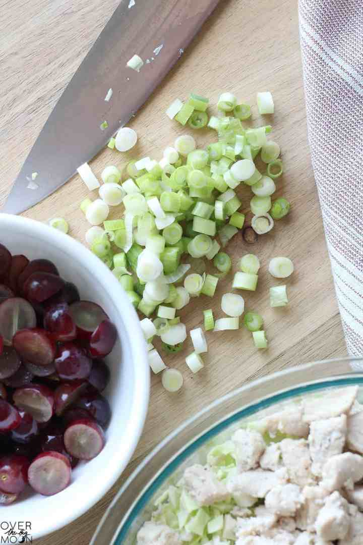 A cutting board with diced green onions on it. Next to them is a white bowl of halved purple grapes and also a clear bowl of cubed cooked chicken.