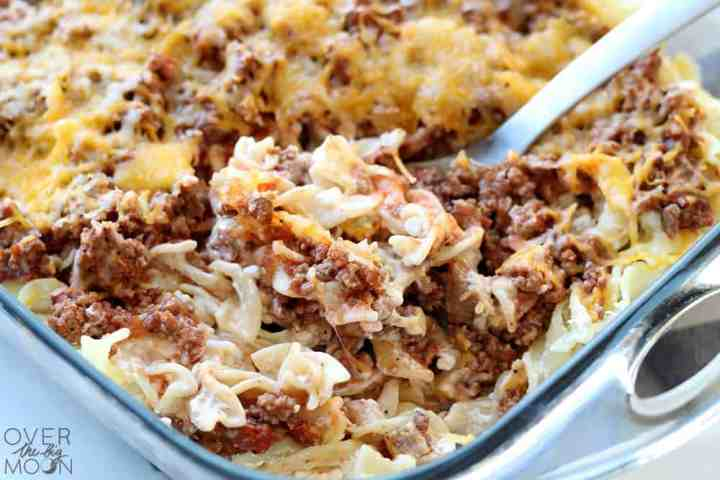 Up close picture of the Sour Cream Noodle Bake casserole made with egg noodles, a hamburger and tomato sauce mixture, topped with shredded cheese.