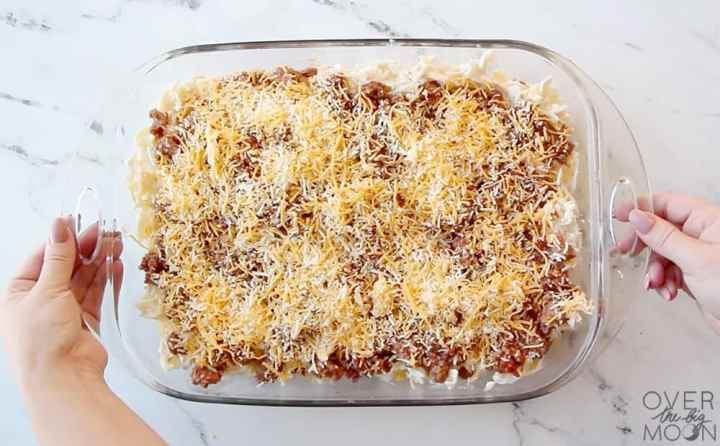 An assembled Sour Cream Noodle Bake in a glass casserole pan. It is made of egg noodles, hamburger mixture and shredded cheese. With two hands on each side of the casserole dish.