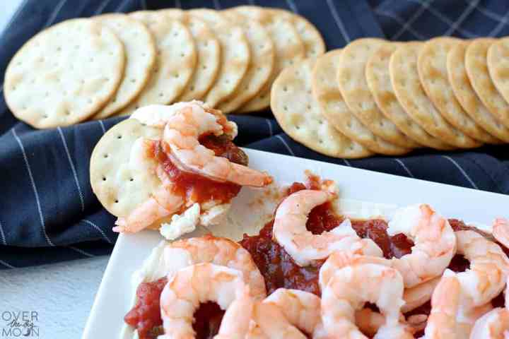 The edge of a white platter with a shrimp dip on it. On the corner is a round cracker with some shrimp dip on it. Above the platter is a black towel with crackers on it.