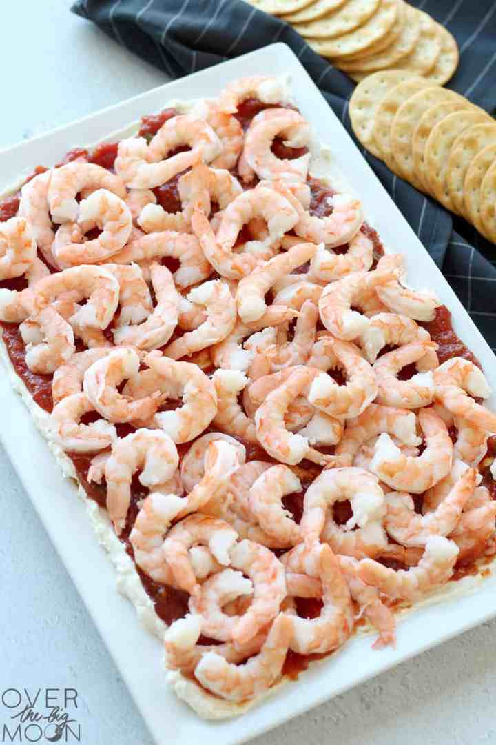 A white platter with a 3 layer shrimp dip on it. In the background is a black towel with crackers on it.