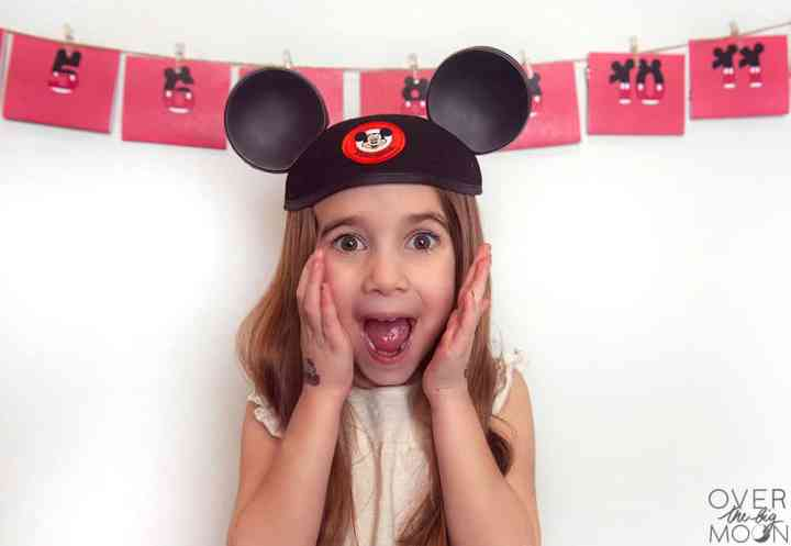 A little girl that is very excited with a Mickey Mouse hat on her head. On the wall behind her is a printable countdown to Disney made up of red envelopes.