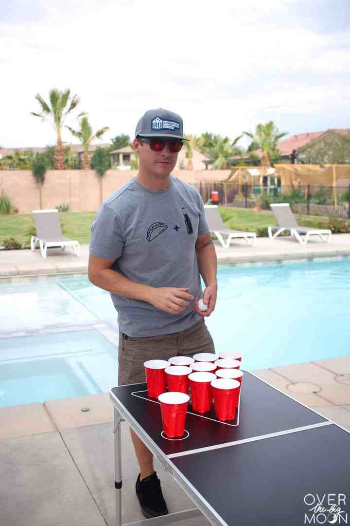 A guy, playing Beer Pong next to a pool. He's wearing a shirt that has a picture of a taco + a bottle of beer.