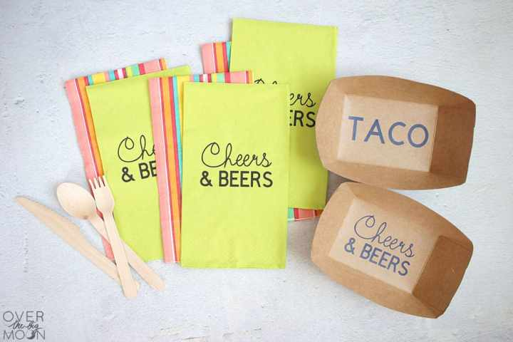 A pile of napkins that are lime green and say Cheers and Beers on them. Under the lime green napkins are colorful napkins. Next to the napkin are brown taco trays that say Taco in vinyl on the bottom of them.