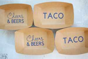 Brown paper serving trays that have navy blue vinyl words added to the bottoms of them that says either Cheers & Beers or Taco.