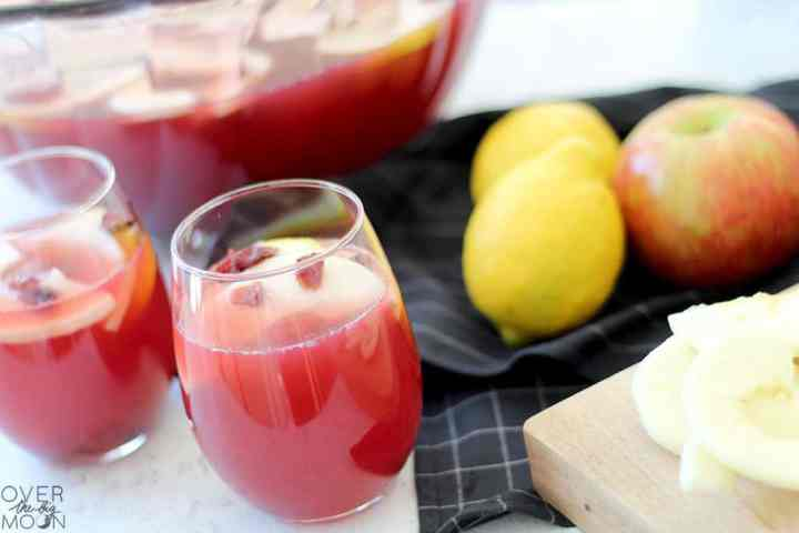 Two cups of red fruit punch, garnished with apple slices and craisins. Behind it is a large bowl of the punch and next to the bowl are a few lemons and apples.