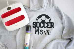 A gray hoodie with a design that says Soccer Mom on it and next to the the hoodie is an EasyPress 2 and roll of Iron On.