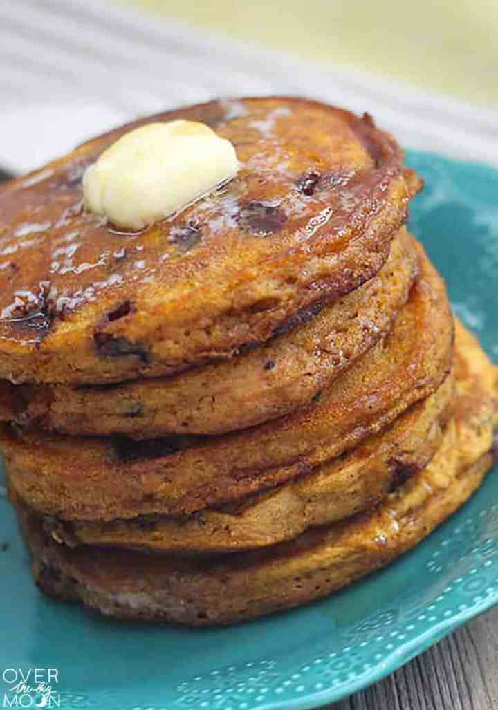 A stack of Pumpkin Chocolate Chip Pancakes on a blue plate. On top of the stack is a cube of butter.