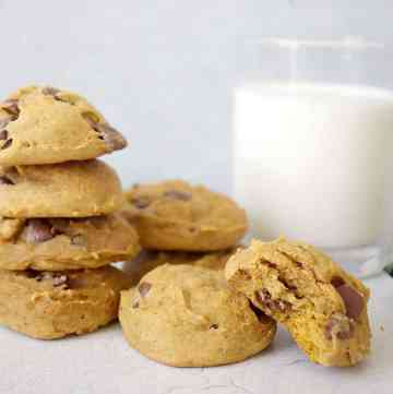8 pumpkin chocolate chip cookies stacked on a white counter. The cookie in the front has a bite out of it. In the background is a glass of milk.