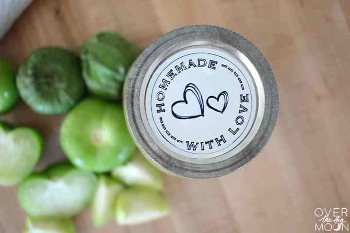 The top of a mason jar, which has a white label on it that says Homemade With Love and some heart shapes. Next to the Mason Jar is a pile of tomatillos, some cut and some not.
