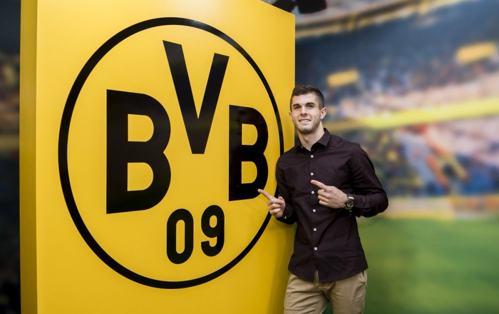 Pulisic in front of the Dortmund logo in their facility