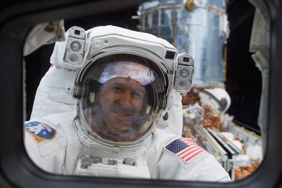 Astronauta John Grunsfeld reparando o telescópio Hubble.