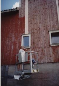 Fra dugnaden på uthuset. Olav Upsahl i liften for å male baksiden av uthuset.