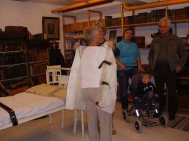 Demonstrasjon av tvangstrøye som tidligere ble brukt innen psykiatrien. Reidun Braathen demonstrerer og Torhild Brenna, lille Jakob og Terje Brenna følger interessert med.