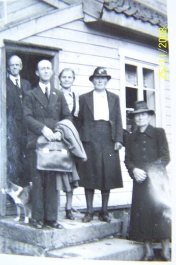 """Bildet er trolig tatt på gården Vollen på Øvrebø hvor Ole Jørgen Horrisland bor nå (2009). Den gang bodde Mari Øvrebø og Alfred Frøyså der. Det kan se ut som om de har hatt besøk av en predikant(?) og nå er de foreviget sammen med sine gjester.Fra venstre Albert Frøyså, ukjent """"predikant"""",Olga Øvrebø, Inga Ilebekk og Mari Øvrebø. Helt til venstre og foran Albert står hunden Frida. Som den buhund den var elsket den og springe etter bilene. Dette ble dens bane da den ble overkjørt og drept av lærer Mindrebø, som forøvrig var helt uten skyld for den triste hendelsen."""
