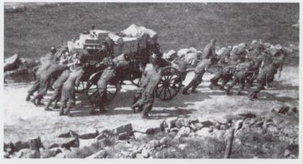 Tyske soldater har kapitulert og er på veg til Evje i mai 1945 etter frigjøringen. Bildet er tatt i bunnen av Vassåsdalen og fangene har sine eiendeler stuet sammen på en kjerre mens noen skyver og noen drar opp den lange bakken.