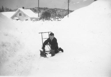 En ung Harald Skuland trever med å få brøyta bort snøen på Setesdalsvegen. Det går bra med spark og brøyteplog som er laget av proffe: Førelands Karosseriverksted!!