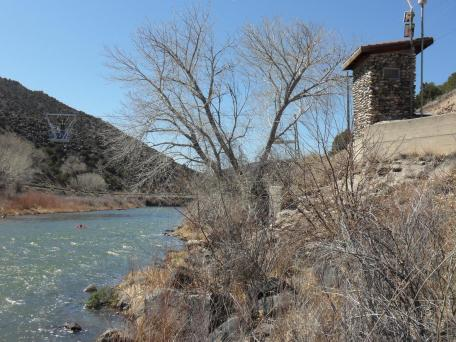 Image of streamgage on the Rio Grande at Embudo. Gage house made of local stone, cableway for measureing flow, riffles, and kayaker in river.