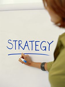 A person writing the word strategy on a whiteboard.