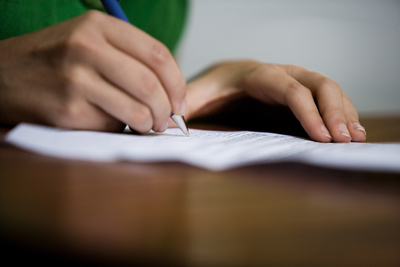 A picture of a person writing on paper.