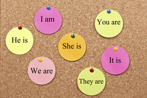 A picture of pronouns written on tags and pinned to a corkboard.