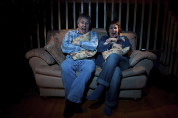 A picture of two people watching a scary movie.