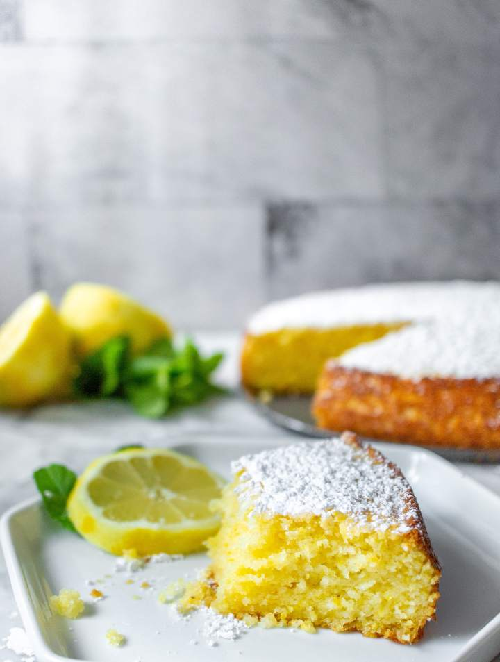 Slice of lemon ricotta cake on a plate with lemon slices