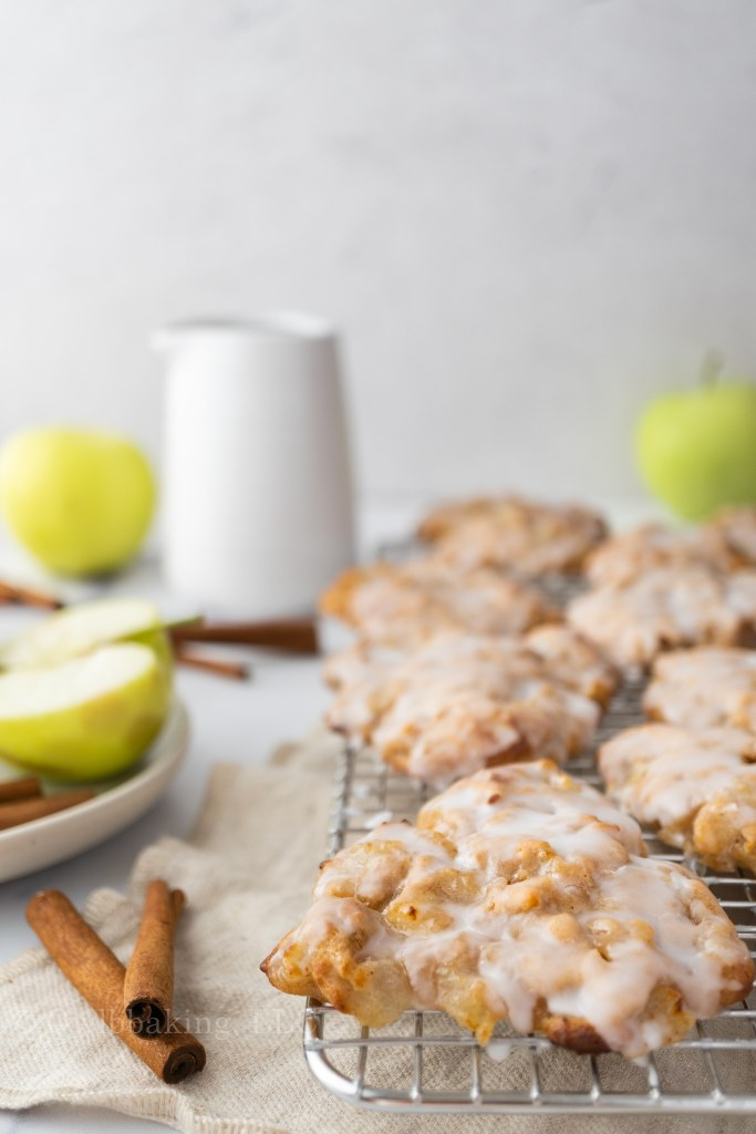 Air Fryer Apple Fritters_on a rack with apples and cinnamon sticks