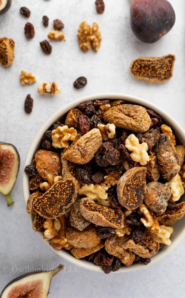 a bowl of dried figs, raisins and walnuts