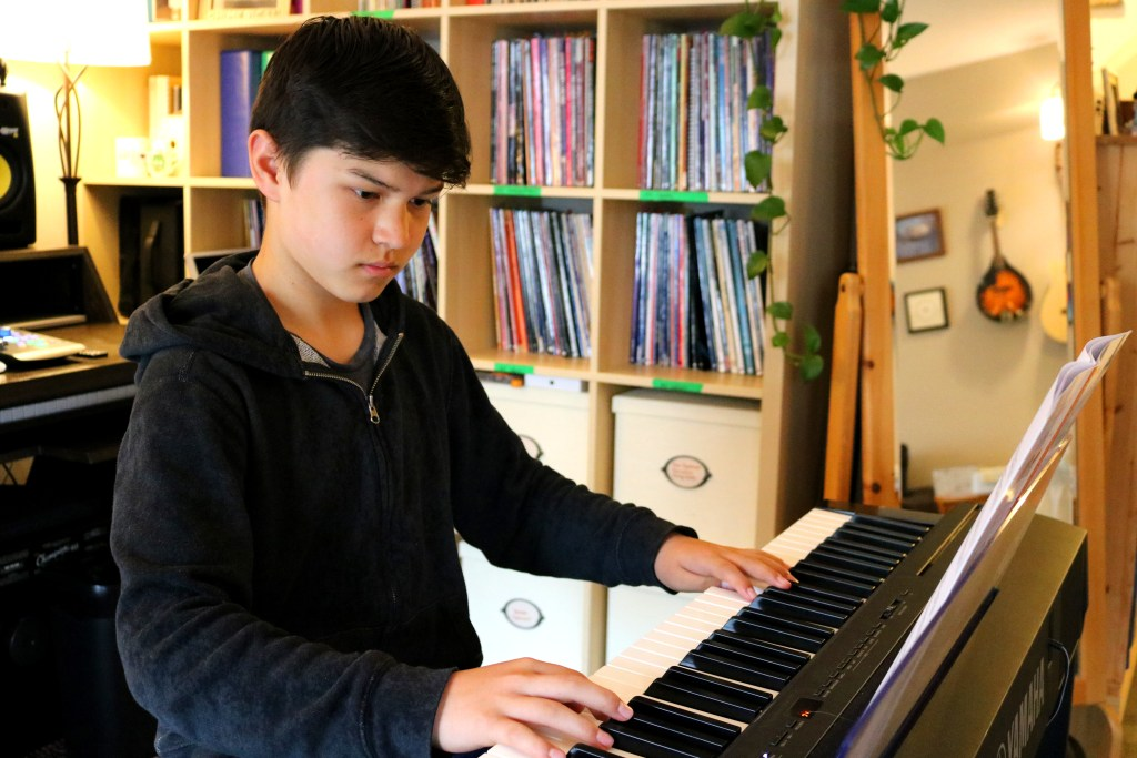 A student of CBY Music playing the piano.