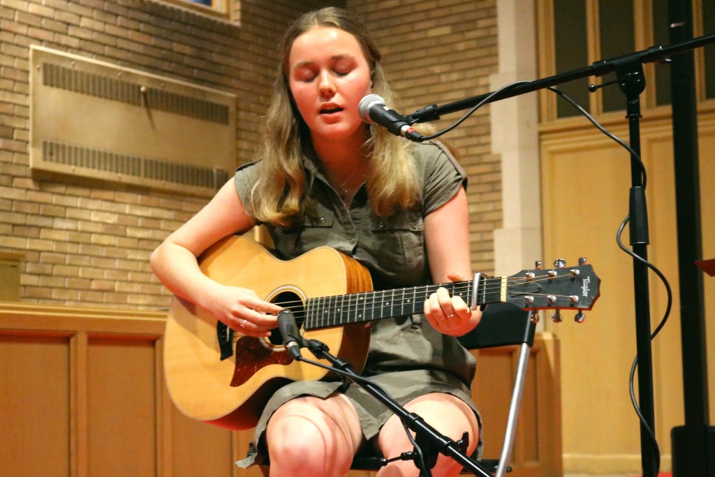 Student of CBY Music Studio singing and playing a guitar on stage.