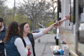 Freshman Laura Benson hands cash to Andrew Tuchow '13 for her food purchase at the Kinetic food truck. Photo courtesy of Spenser Hickey.
