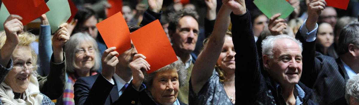 People holding up orange and green voting cards at the Oxford Union debate