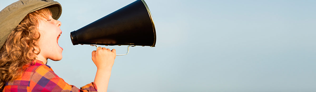 A little boy with long, curly blonde hair shouts into a megaphone