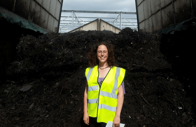 GFO staff member in front of a huge pile of compost