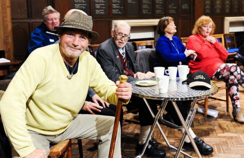 Group of older people having coffee - one man sits holding stick looking directly at camera