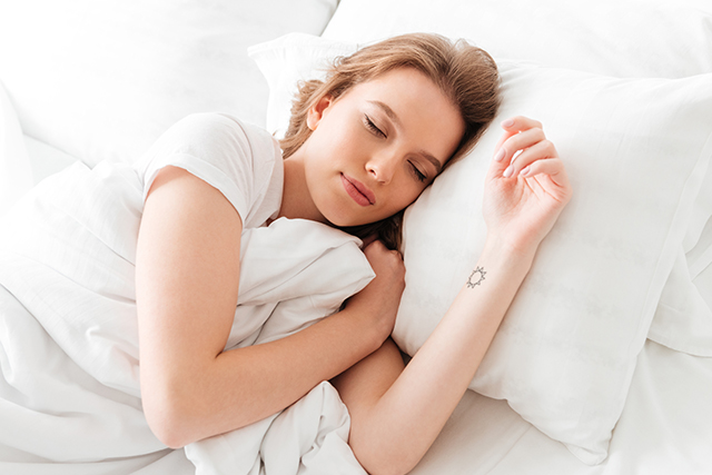 Sleeping young woman lies in bed with eyes closed.