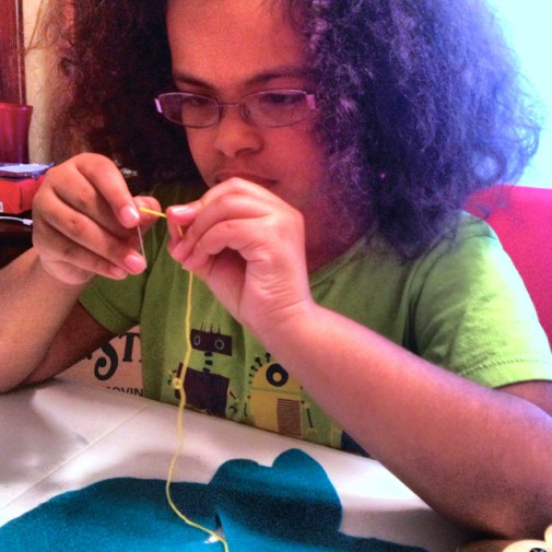 Learning to sew must begin with threading the needle.